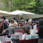 La gente pasea a través de los puestos de libros